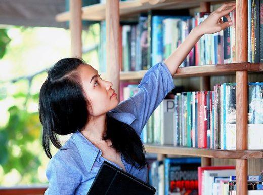 Chica estudiando para la selectividad buscando libro en la biblioteca